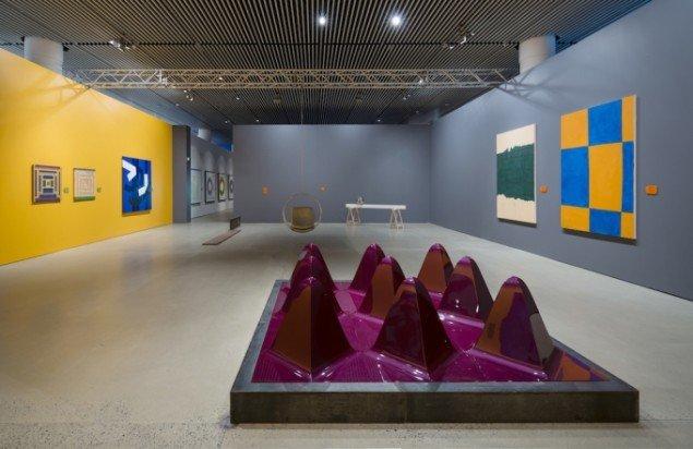 Installationsview med Förgs malerier til højre. Bemærk Rosti-brætterne. I forgrunden Hein Heinsen. Foto: Anders Sune Berg